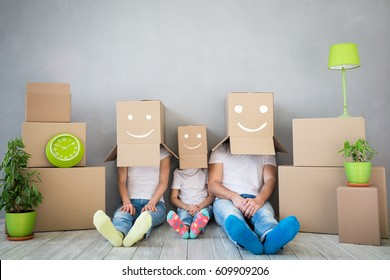 "Happy family playing into new home. Father, mother and child having fun together. Moving house day and ""think outside the box"" concept"