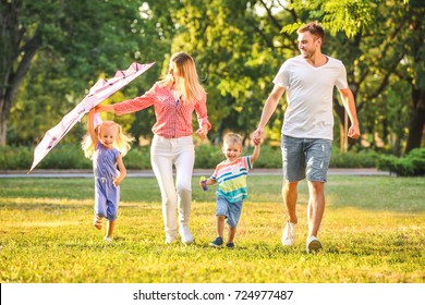 Happy family playing with kite in park on sunny day