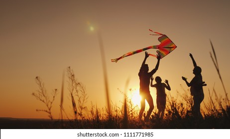 Happy family playing with a kite at sunset. Mom, Dad and daughter are happy together