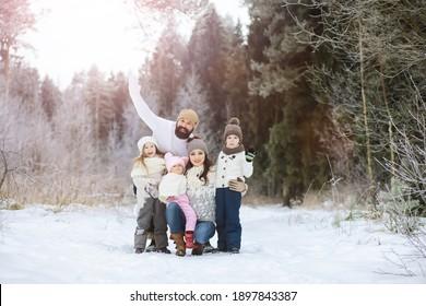 Fröhliche Familie spielt und lacht im Winter im Schnee im Freien. Stadtpark Wintertag.