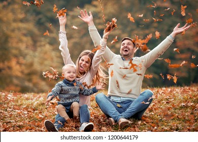Happy family playing with leaves in beautiful autumn park.