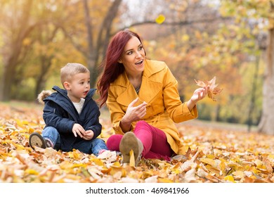 Happy family playing with leaves and having fun at autumn park