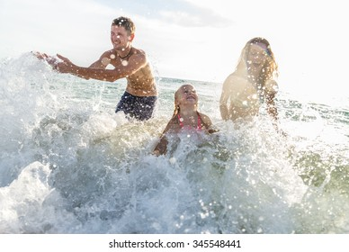 Happy family playing in the ocean and splashing water - Tourists on vacation on a tropical island