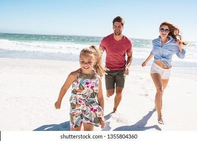 Happy family playing on the beach. Beautiful daughter running on the beach with mother and father in a bright sunny day. Smiling young family in casual having fun at sea.