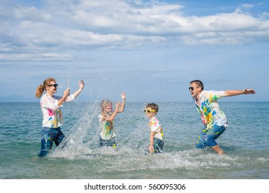 Happy family playing on the beach at the day time. People having fun outdoors. Concept of friendly family.