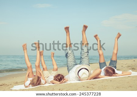 Happy family playing  on the beach at the day time. Concept of friendly family.