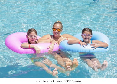 Happy Family playing on inflatable tubes in a swimming pool on a sunny day