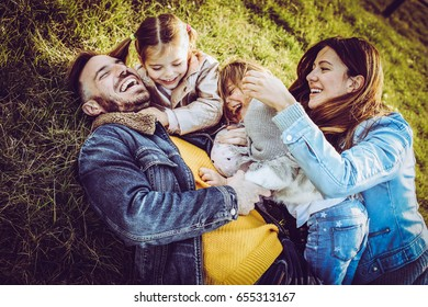 Happy family playing outdoor. Family lying and playing on the grass.