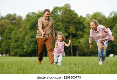 Happy family playing in the park. Emotional and funny dad and mom are running on the grass for their happy and active blonde daughter during the summer holidays. Childhood.Positive emotions. Lifestyle