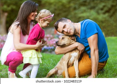 happy family playing in the park with his dog
