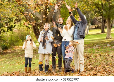 Happy family playing in the park together on an autumns day