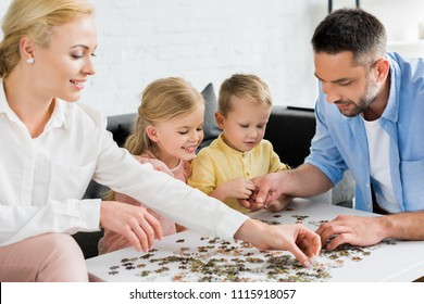 happy family playing with puzzle pieces at home