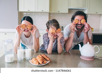 Happy family are playing with rolls. They pyt them on eyes and smiling. Family are leaning to table. There are kettle, milk and croissans on it.