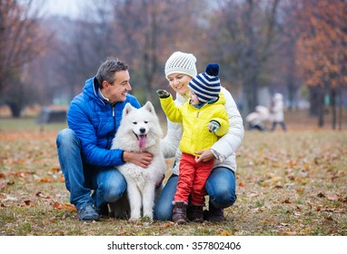 Happy family playing with a samoyed dog in autumn park