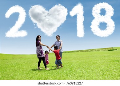 Happy family playing together in the park with clouds shaped numbers 2018 and heart in the sky