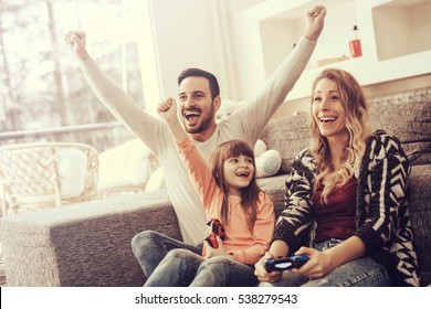 Happy family playing video games at home and having fun together.