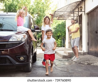 Happy family playing while washing car outdoors