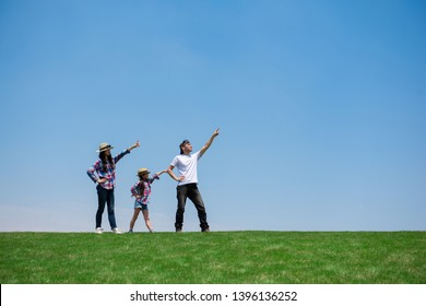 Happy family pointing at the sky in the meadow