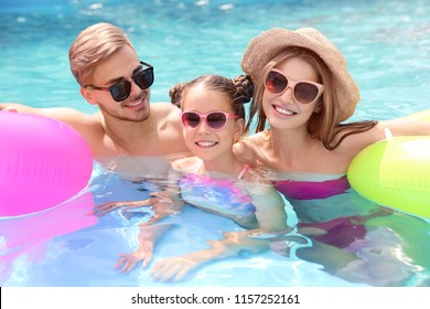 Happy family in pool on sunny day