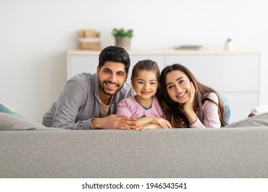 Happy family portrait. Happy arab mother, father and daughter cuddling and smiling to camera on couch at home. Fam spending time together on weekend, enjoying staying at home