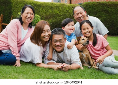 Happy family portrait. Chinese family are lying on the grass in their garden, smiling for the camera with their pet dog.