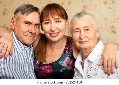 Happy family. Portrait of elderly couple and adult daughter happily looking at camera. Senior man, woman with their caregiver at home.