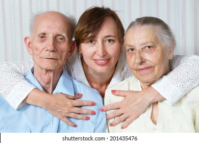Happy family. Portrait of elderly parents and adult daughter happily looking at the camera. Senior man, woman with their caregiver at home. Concept of health care for elderly old people, disabled.