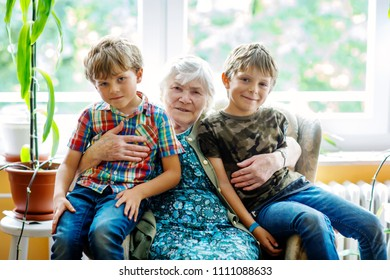 Happy family portrait with grandmother and two grandsons. Grand grandmother sitting with two school kid boys at home