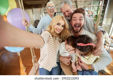 Happy family portrait with grandparents at home; Happy family offspring concept