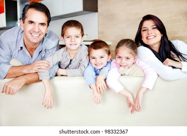 Happy family portrait leaning on the sofa and smiling