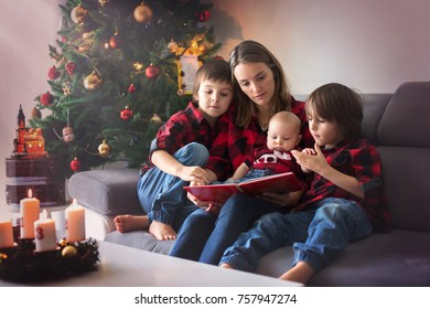 Happy family portrait on Christmas, mother, reading a book to her three children sitting on couch at home, chritmas decoration around them
