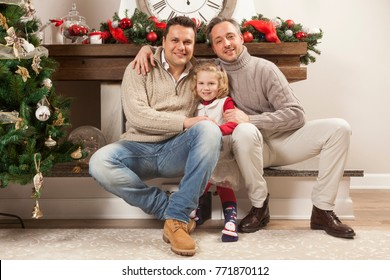 Happy family portrait on Christmas, gay male couple and one child sitting near fireplace at home, chritmas decoration around them