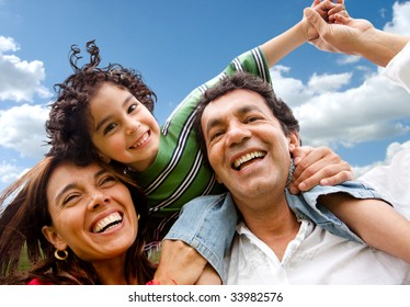 happy family portrait outdoors smiling with a blue sky