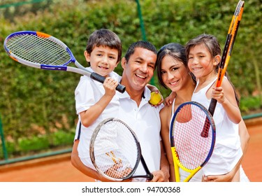 Happy family portrait playing tennis outdoors and smiling