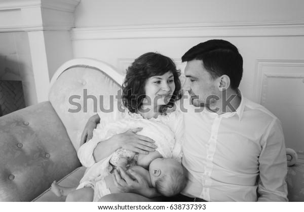 happy family portrait. proud dad. Mother breastfeeding her baby son. Happy motherhood concept. Little baby boy breast feeding.