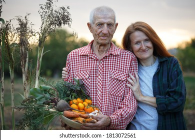 happy family. portrait of smiling senior man  and granddaughter at the garden