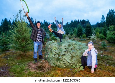 Happy family posing with fresh cut Christmas tree at farm