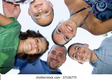 A happy family posing in a group huddle formation.