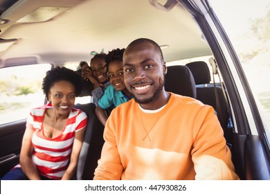 Happy family posing together in car