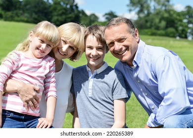 Happy family posing with two children at outdoors