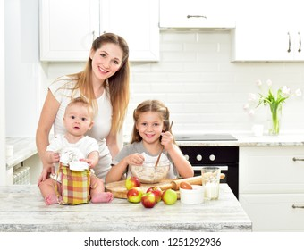 Happy family are preparing bakery together. Mother, daughter and baby are cooking cookies and having fun in the kitchen. Homemade food.