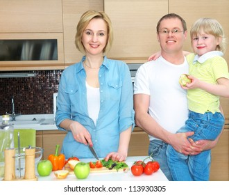 Happy family is preparing a healthy dinner in the kitchen. Mother cuts  vegetables