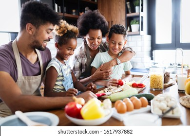 Happy family preparing together food in the kitchen - Shutterstock ID 1617937882