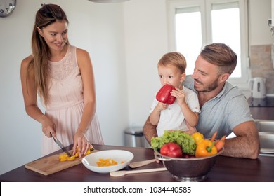 Happy family preparing vegetables together at home in the kitchen.