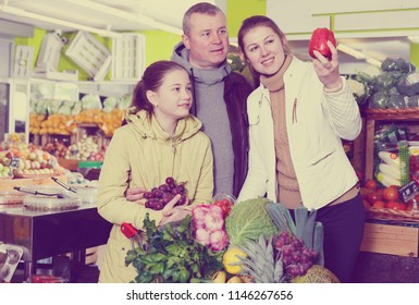 Happy family with preteen daughter in search of fresh apples in fruit store