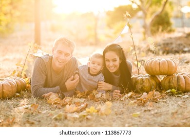 Happy family with pumpkin on autumn leaves. Outdoor.