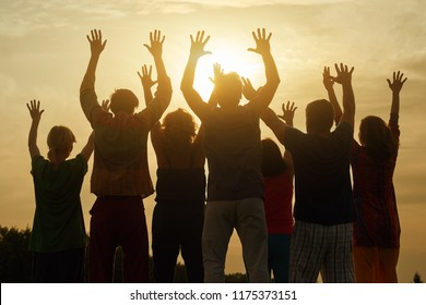 Happy family raised hands up on the sky at sunset. Dark black shadow of people with hands up.