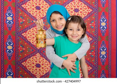 Happy Family in Ramadan - Two Muslim sisters celebrating Ramadan - playing with Ramadan lantern in front of Ramadan background