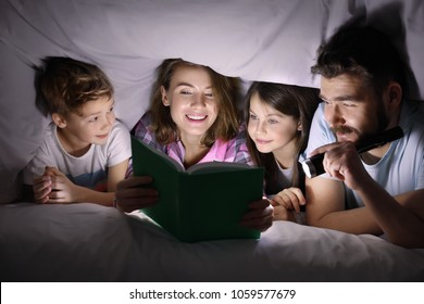 Happy family reading bedtime story under blanket in evening
