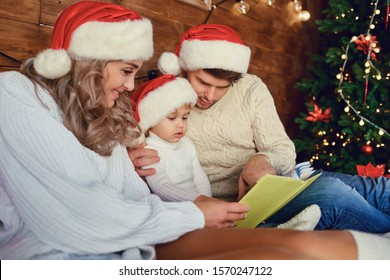 Happy family reading a book at Christmas.